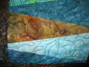 Batik fabrics.. so variable. This also shows the quilting pattern, which plays off the motifs of the backing fabric.